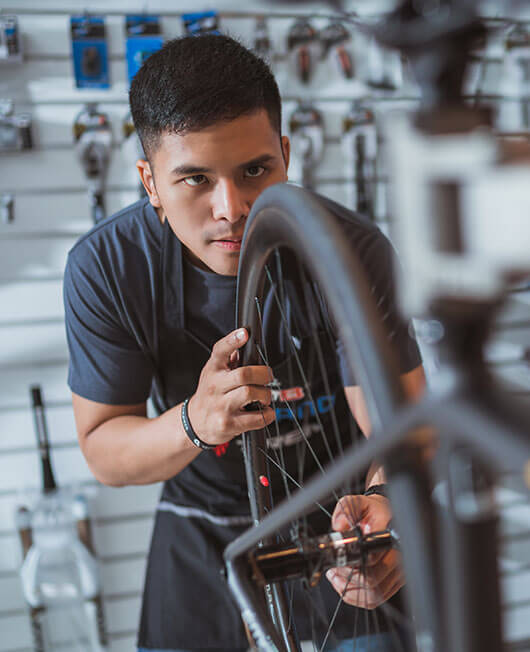 A young bicycle mechanic apprentice fixing a wheel