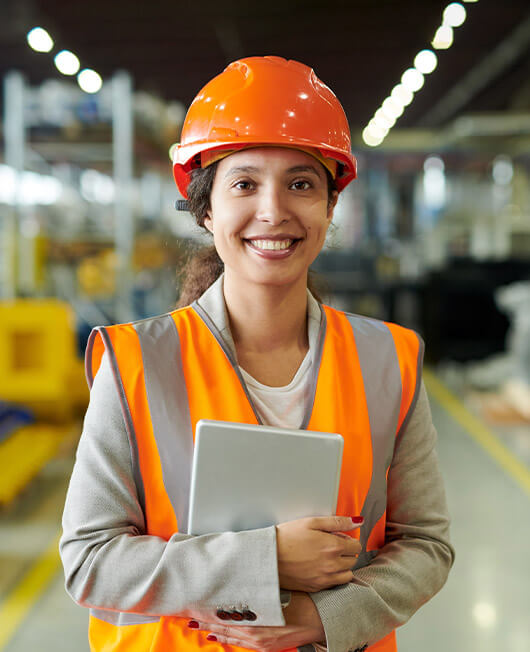 A female engineering worker in an orange hard hat and high visibility vest in a factory