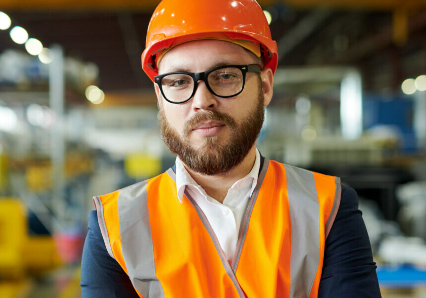 A male engineering worker in an orange hard hat and high visibility vest in a factory