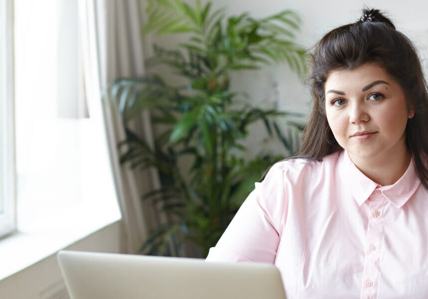 A girl in a modern lounge in pink shirt using a laptop