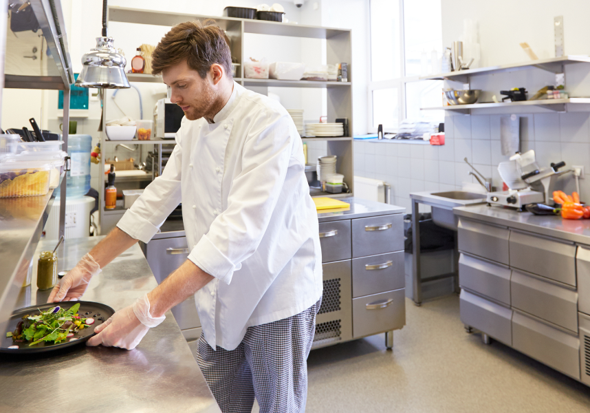 A man in a chefs jacket working in a kitchen preparing a salad
